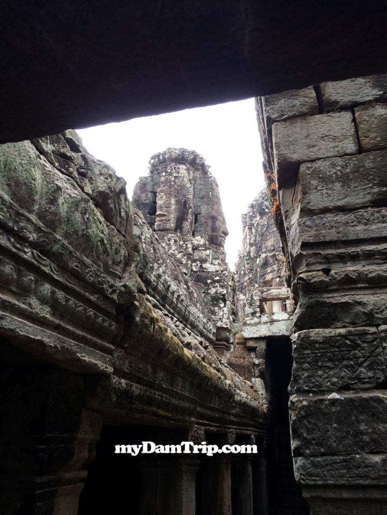 Peeking Through Narrow Corridor Showing Faces In Tower Angkor Thom